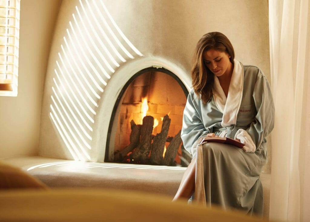 Woman in robe writing in journey next to lit fireplace in suite