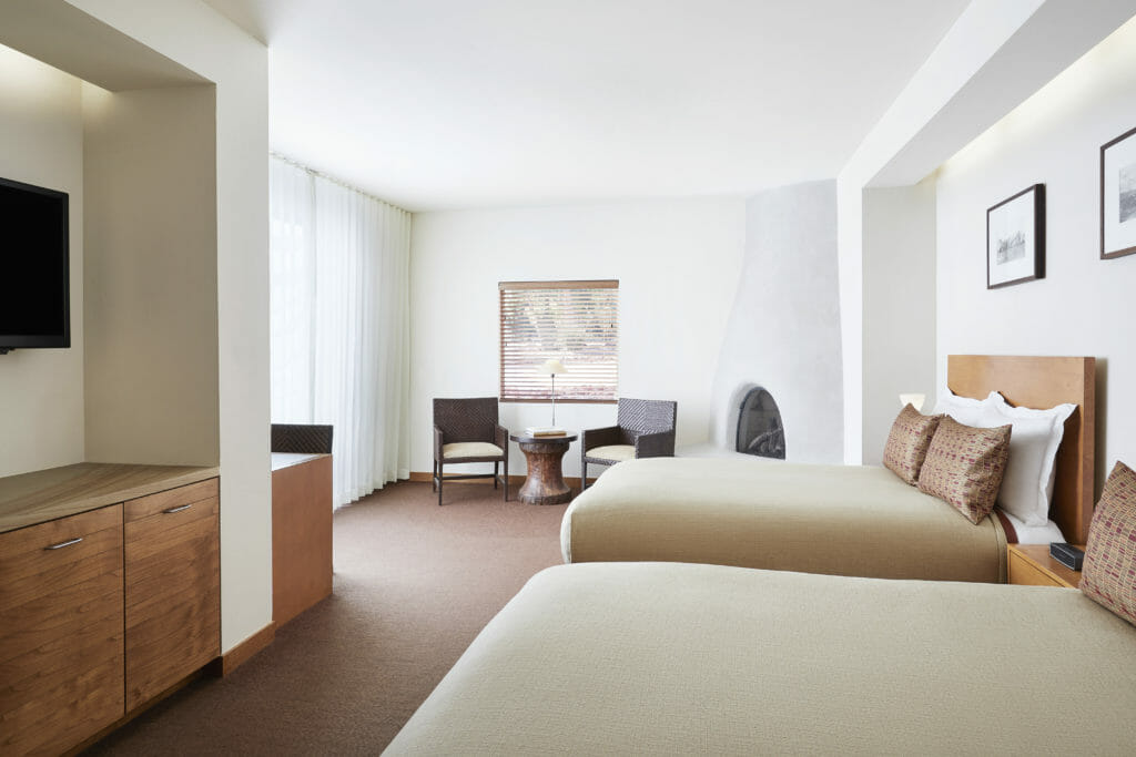 two empty gray beds inside white painted room