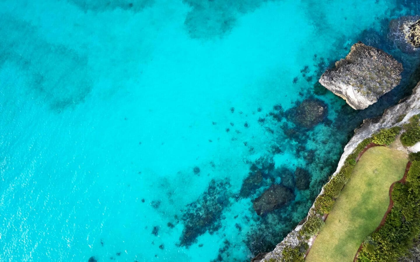 aerial photography of body of water by rock formation at daytime