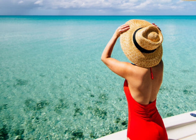 woman wearing red one-piece swimsuit looking at sea