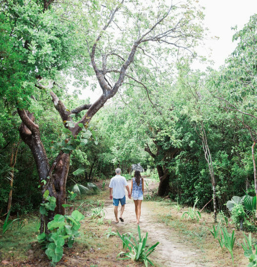 man and woman holding each others hands walking near green trees