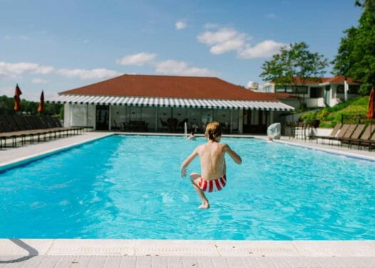 boy in mid-air about to jump into swimming pool