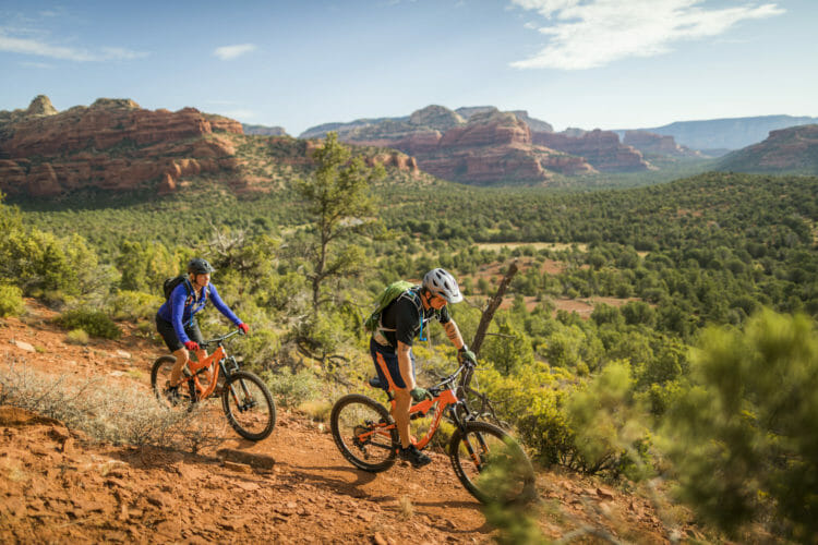 man in bike gear riding bicycle ahead of a woman through the Red Rocks