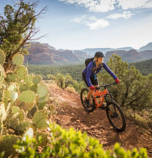 woman in biking gear riding a bicycle downhill through the Red Rocks